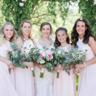 A stunning wedding party of bridesmaids in soft pink dresses with elegant floral bouquets.