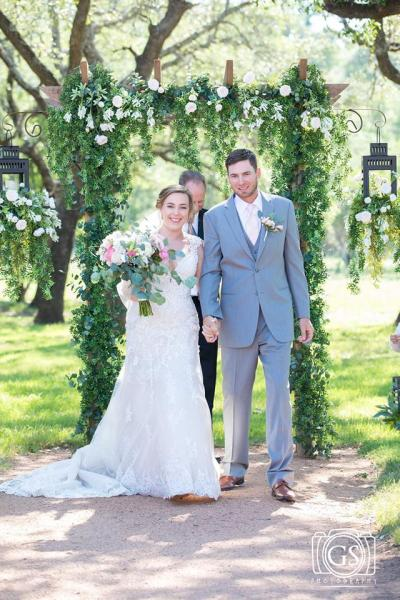 These two love birds just tied the knot beneath a stunning green archway!